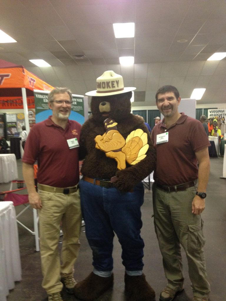 Drs. Brian Bond and Henry Quesada enjoy Smokey Bear's visit to the SBIO Department booth.